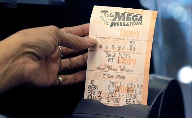 Anita Watson, assistant manager at Energy Express convenience store, prints out a Mega Millions lottery ticket Monday, Dec. 16, 2013, in St. Louis. The Mega Millions jackpot soared to $586 million on Monday amid a frenzy of ticket purchases, a jump that pushed the prize closer to the $656 million U.S. record set last year. (AP Photo/Jeff Roberson)