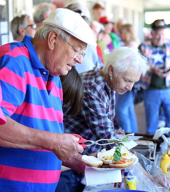 Carson City resident Tom Tomashek makes a plate of food at the annual free Memorial Day barbecue hosted by Evergreen Gene's on Monday.