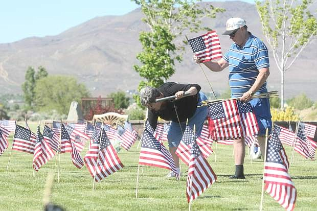 Four-year-old Natalie Duenas helps post flags at Lone Mountain Cemetery on Friday afternoon.