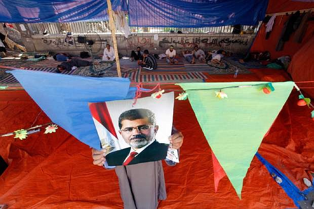 """A supporter of Egypt's ousted President Mohammed Morsi hangs his poster at a tent in Nahda Square, where protesters have installed their camp near Cairo University in Giza, southwestern Cairo, Egypt, Monday, Aug. 12, 2013. Egyptian authorities on Monday postponed a move to disperse two Cairo sit-ins by supporters of the country's ousted president to """"avoid bloodshed,"""" an official said, as Islamist supporters stepped up rallies to demand his return to power. (AP Photo/Amr Nabil)"""
