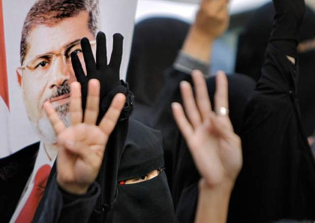 Supporters of Egypt's ousted President Mohammed Morsi, pictured, raise their hands and four fingers, a sign that protesters say symbolizes the Rabaah al-Adawiya mosque in Cairo that was cleared last week by Egyptian security forces, during a march in the Maadi district in Cairo, Egypt, Monday, Aug. 19, 2013. (AP Photo/Amr Nabil)