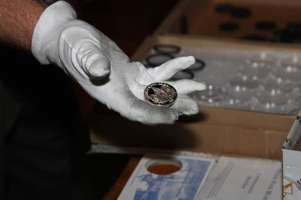 Ken Hopple displays a freshly pressed coin on Friday at the state museum in Carson City.