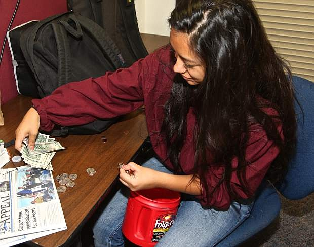 Daniela Dominguez counts $50 donated by Mrs. Golik's government class to the family of Cameron St. Hilaire.