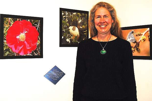 Edith Isidoro-Mills stands proudly in front of her macro photographs.