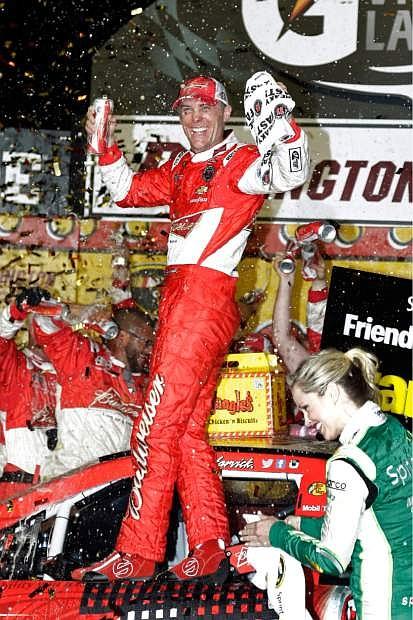 Kevin Harvick celebrates in Victory Lane after winning the NASCAR Sprint Cup auto race at Darlington Raceway in Darlington, S.C., Saturday, April 12, 2014. (AP Photo/Chuck Burton)