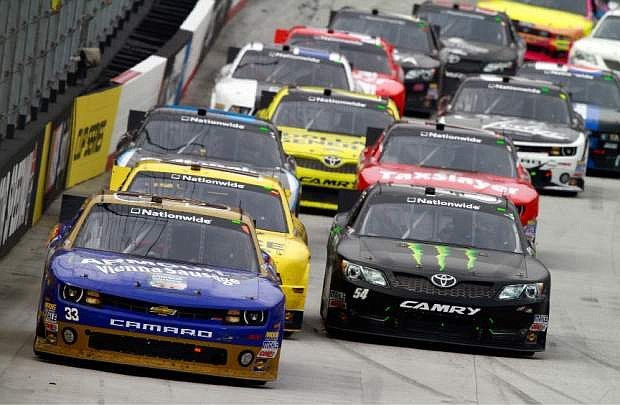 Kevin Harvick (33) leads Kyle Busch (54) and the rest of the field during the NASCAR Nationwide Series auto race Saturday, March 16, 2013, in Bristol, Tenn. Busch won the race. (AP Photo/Wade Payne)