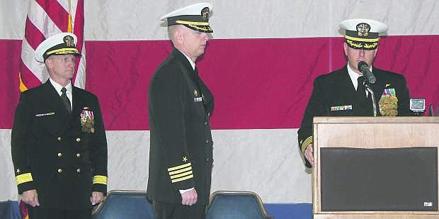 Capt. David Halloran, right, reads his orders on Friday  to become the new commanding officer of Naval Air Station Fallon as Rear Adm. Mark Rich, left, and Capt. Leif Steinbaugh, the outgoing commander, look on.