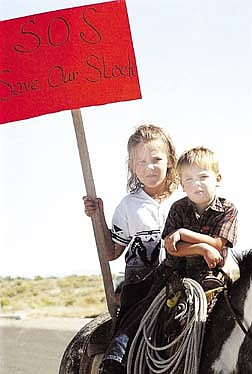 Arden Bundy,3, right, and his sister Stetsy Bundy, 8, ride a horse while carrying a protest sign, in front of the Fallon Livestock Auction in Fallon, Nev., Tuesday, July 31, 2001. About 50 ranchers and states' rights activists and their supporters picketed the livestock auction yard Tuesday, protesting the federal government's seizure of cattle from two ranchers accused of trespassing on public lands. (AP Photo/Lahontan Valley News, Heather Singer)