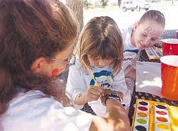 Brian CorleyCarli Smith, 12, right, watches as Leslie Romine, 4, paints with water colors on AnneMarie Bozin, 10, during the National KidsDay at the Boys & Girls Club on Sunday.