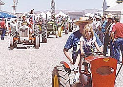 Brian Corley Amanda Nelson, 7, drives a tractor with her grandfather, Don Nelson, during the tractor show Saturday. The event continues today at the Johnson Lane home of Bill and Dorine Ramsden.