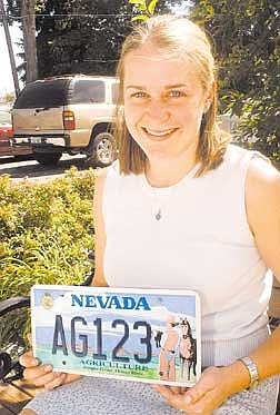 Brian Corley photo.Heather Dye, executive secretary of the Nevada Future Farmers of America, displays one of the new agriculture license plates.