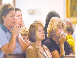 Terri Domitrovich, left, Marilee Swirczek and Catherine Boedenauer mourn the loss of lives from the terrorist attacks at a noon mass at St. Terressa's. Photo by Brian Corley