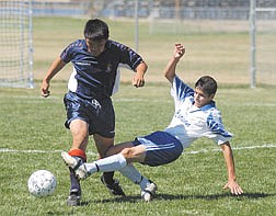 Carlos Hernandez takes the ball away from a Reno High School defender late in the first half. Carson came from behind to win 3-2. Photo by Brian Corley