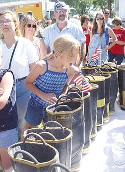 Katy Runde, 11, looks in a money-filled boot at a barbeque organized by the Carson City Fire Department. The barbeque was held in an effort to try and raise money for New York City firefighters. Photo by Brian Corley