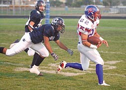#22 for Reno High School runs past Carson High School #1 during the homecoming game. Photo by Brian Corley