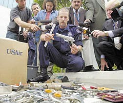 Los Angeles Police Officer Robert Rios holds-up a plastic gun as he displays knives, hammers, screwdrivers, kitchen untensils and other weapon-like  items confiscated from passengers that are no longer permitted in carry-on baggage Tuesday, Sept. 18, 2001, at Los Angeles International Airport. More than 5,000 items a day are confiscated during intensive screening techniques at security checkpoints around LAX. Federal inspectors who uncovered lapses in airport security over the last decade proposed fines in just one-quarter of the cases, a record critics say underscores weaknesses in oversight of the system that protects the nation's air travelers. (AP Photo/Nick Ut)