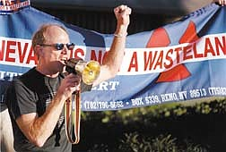 """Bob Fulkerson, of the Progressive Leadership Alliance, stands in front of a """"Nevada Is Not A Wasteland"""" banner as he leads an anti-nuclear dump rally in Reno, Nev. on Thursday, Oct. 4, 2001. Fulkerson and others staged the protest against a proposed nuclear dump site at Yucca Mountain during a public hearing on the project. (AP Photo/Debra Reid)"""