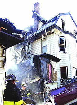 Firefighters look thorugh debris that landed in the backyard of a house at at the scene of the crash of an American Airlines jetliner en route to the Dominican Republic with 255 people aboard crashed moments after takeoff from Kennedy Airportin the Queens borough of New York, Monday, Nov 12, 2001. (AP Photo/John-Marshall Mantel)