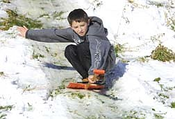 Timmy Karpe, 10, of Carson City, Nev., rides his shovel down a sled hill in a park on Monday morning, Dec. 3, 2001.  Carson City area kids took advantage of no school from a scheduled teacher workday and snowfall ranging from six inches in the valley to two feet at the higher elevations. (AP Photo/Nevada Appeal, Cathleen Allison)