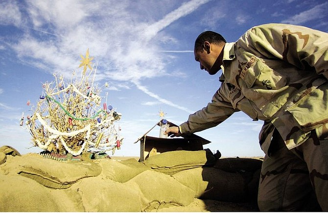 Gunnery Sgt. Aniceto Hernandez, from Bakersfield, Calif., adjusts an angel made of a water bottle on the Nativity scene he constructed from a ration box at the edge of his fox hole on Camp Rhino, Afghanistan, Saturday, Dec. 15, 2001.  Hernandez and his Marines also made a Christmas tree from a local bush, left, and decorated it Marine-style: shotgun shells, bullets and water bottle caps. (AP Photo/Earnie Grafton, Pool)
