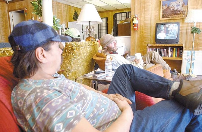 John Taylor, left, and Steven Lakey watch television at the Jubilee Center where people can come to get support for different problems whether they are depressed, suffer from a mental illness or are just out of work. Photo by Brian Corley
