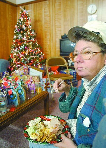 Lin Lennon sits in the Jubilee Center in front of a Christmas tree eating her free Christmas dinner. The center, which helps those in need, gave out a free dinner to its members who have sought help. Photo by Brian Corley