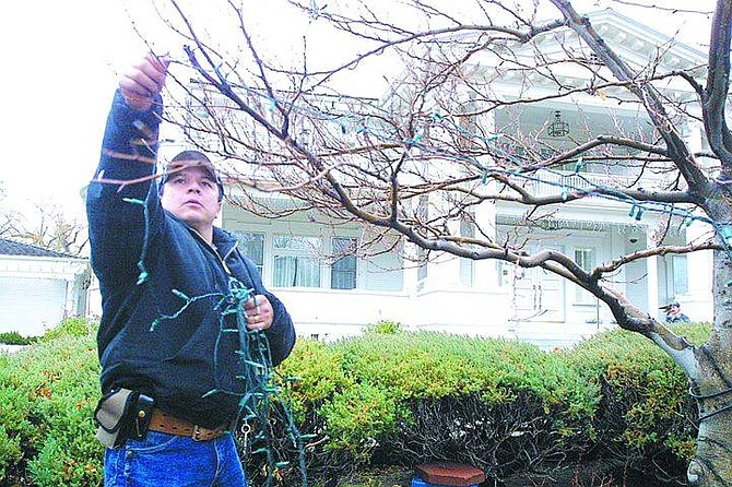 Cathleen AllisonBuildings and Grounds maintenance worker Jose Aguirre takes down Christmas lights in front of the Governor's Mansion on Wednesday afternoon.