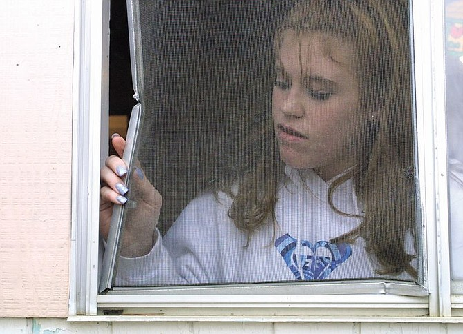 Daycare aide Tiffany Hudder, 15, looks at a damaged screen at the Little Tykes Child Care Center on South Roop Street on Wednesday afternoon.  The business was burglarized Tuesday night.