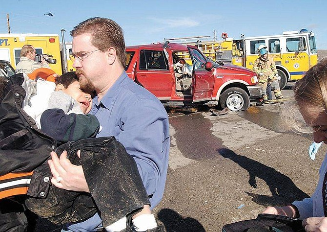 Rick Gunn photoA bystander carries one of two children involved in a traffic collision on Thursday. The children were unhurt, but their mother was injured.