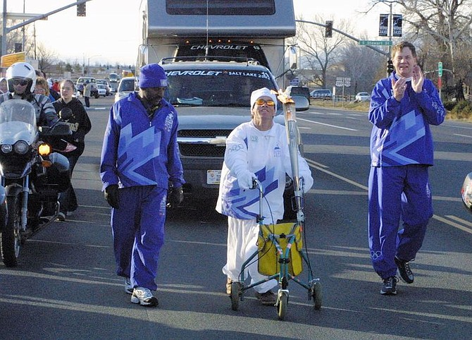 Glen Lucky, 48, of northern Nevada, carries the Olympic torch through a section of downtown Carson City, Nev., Monday, Jan. 21, 2002.  Lucky, who suffers from cerebral palsy, is a well known local who drew a large group of spectators.  (AP Photo/Nevada Appeal, Cathleen  Allison)