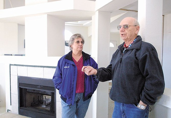 Margaret and Jack Ruckman discuss problems they've had trying to occupy their manufactured home off Goni Road. City officals won't let the couple move into their home because the roof isn't steep enough to meet city code. Photo by Cathleen Allison