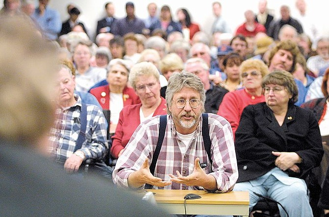 Charles Martins, center, questions the Public Utilities Commission of Nevada on Monday night during a consumer session in Carson City.  A capacity crowd of mostly disgruntled energy customers filed in to protest a proposed rate hike.