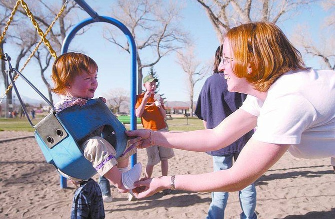 Two-year-old Autumn giggles as mom Joyce Keith takes off the girl's socks as she rides the swingat Mills Park. Photo by Brian Corley/Nevada Appeal