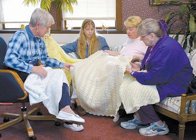 Photo by Cathleen AllisonVolunteer afghan makers, from left, Donna Peak, Barbara Spears, Jackie Welch and Millie Tlachac look through some of the 91 donated baby afghans intended for children born to fathers killed in the New York City terrorist attacks. Peak organized the effort which attracted 75 knitters, but is still looking for a way to get the afghans to children in New York City.