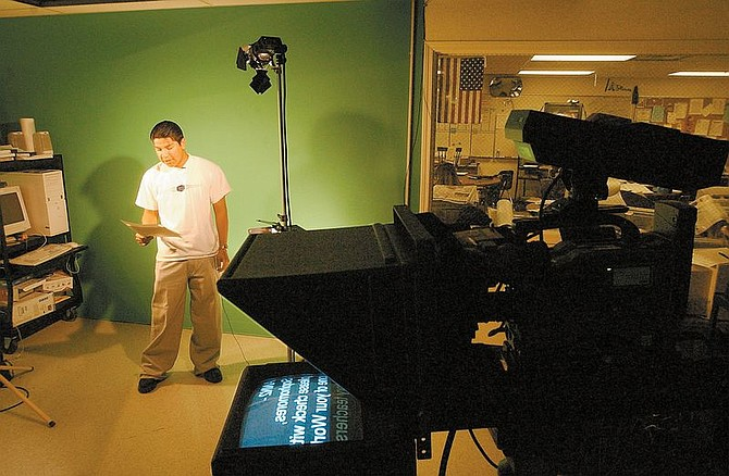 CHS student Jesus Ramirez reads the  announcements in Spanish during a school wide broadcast.  The bilingual portion of the School broadcastl orininates from Video instructor Brian Reedy's studio within the school.