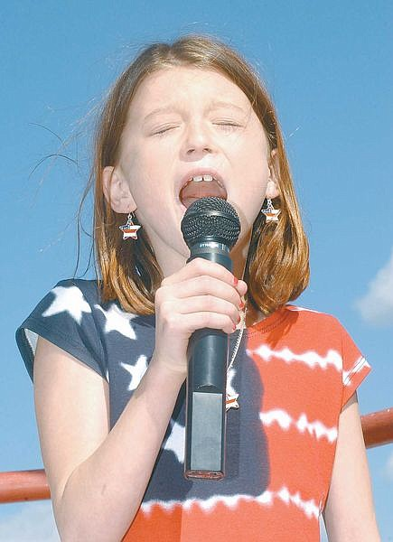 Cethe Choux, 9, sings the Star Spangled Banner at Champion Speedway's opening day Sunday.