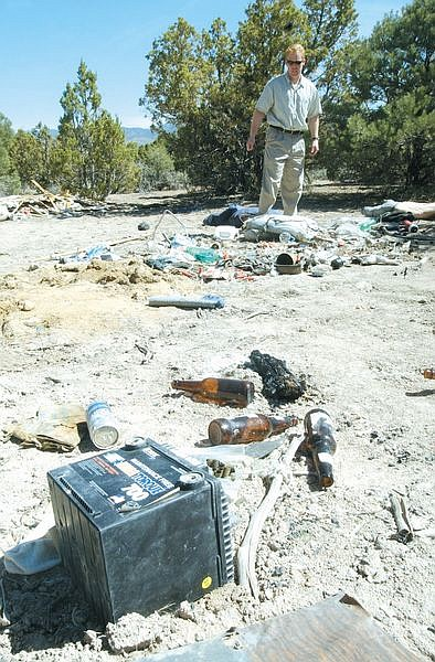Kevin Walsh, President of the Pinenuts Mountian Trail Association, looks over trash left behind at an illegal dump site along Pine Nut Road in Gardnerville. Walsh has organized a clean-up effort to remove some of the garbage planned for June 1st. Photo by Brian Corley