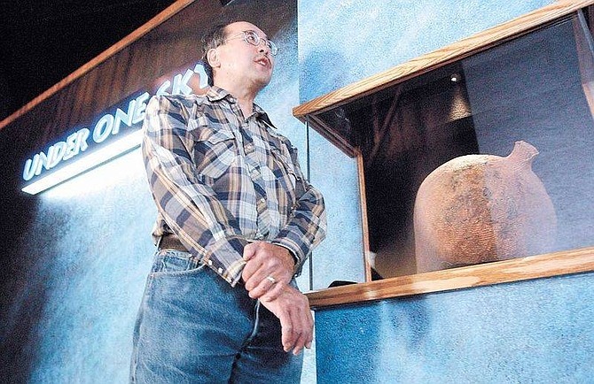 Photo by Rick GunnEugene Hattori, PH.D. and curator of Anthropology for the State of Nevada stands near and early water container on display for tyhe Under One Sky exhibit which is under construction at the Nevada State Museum.