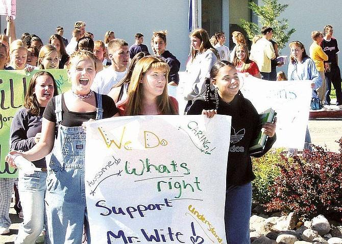 Photo by Kurt HildebrandAshley Gray, 15, Brittanie Tushay, 15 and Crystal Bell, 16, march outside Dayton High School on Thursday.