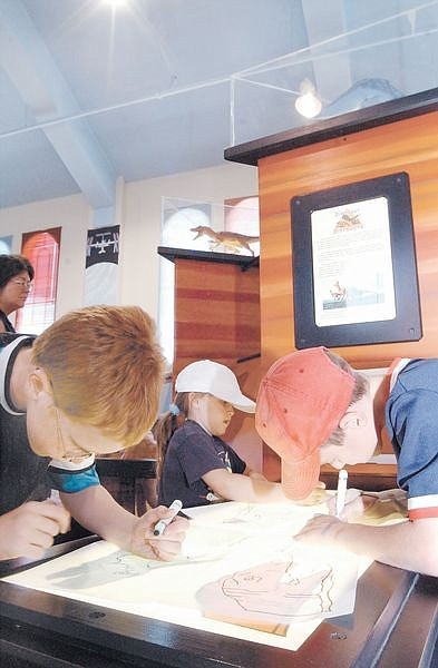 Left to right, Ben Packham, 8, Zoe Beth, 6, and Derek Reilly, 8, trace different dinasours on the new Dinasour Discovery interactive exhibit at the Children's Museum of Northern Nevada. The interactive exhibit will be at the Museum until sept 15th.