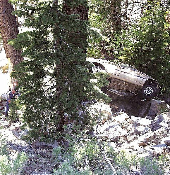 Photo by F.T. NortonA Nevada Highway Patrol trooper stands near the wreck of a gold Toyota last seen driven by Michael Roberts.