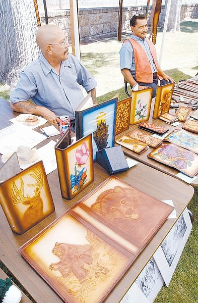 Nevada State Prison inmates Michael Doyle, left, and Hect or Castellon display some  of their leather artwork at a Prison Art Show Tuesday morning. The Art Show was open to the public and included art, poetry and refresments.