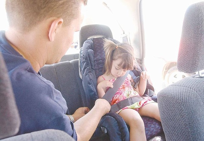 Bryon Hunt, left, installs a car seat properly as Maya Vasquez, 3, looks on Saturday at Western nevada Community College. Photo by Brian Corley