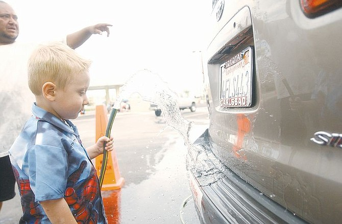 Daniel Morrison, 3, washes soap off a minivan at car wash to raise money for his cancer treatments Sunday as his mother's fiance, EZ Ugarte, helps point out palces for him to wash off more soap. Morrison has already had two surgeries and will under go an MRI on Tuesday in Sacramento, Calif. to get an update on his cancer. Photo by Brian Corley