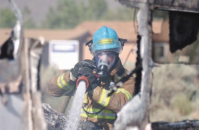 Photo by Brian CorleyCarson City Firefighter, Jim White, sprays water on a trailor that burned in South Carson on Monday afternoon. The trailor and all of its items are believed to be a total loss.