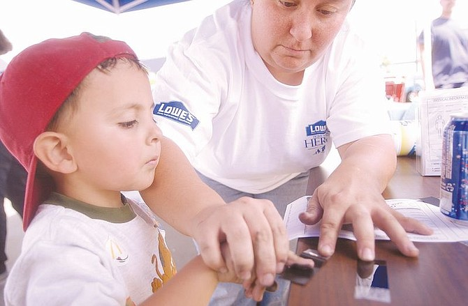Johnathan Lessard, 4, left, watches as his mother, Denise Lessard, puts ink on his fingers while he has his finger prints recorded at Lowes Saturday during a Safety Day for Kids.Hundreds of parents had their childrens' finger prints recorded to help track them in the event of an abduction. Photo by Brian Corley