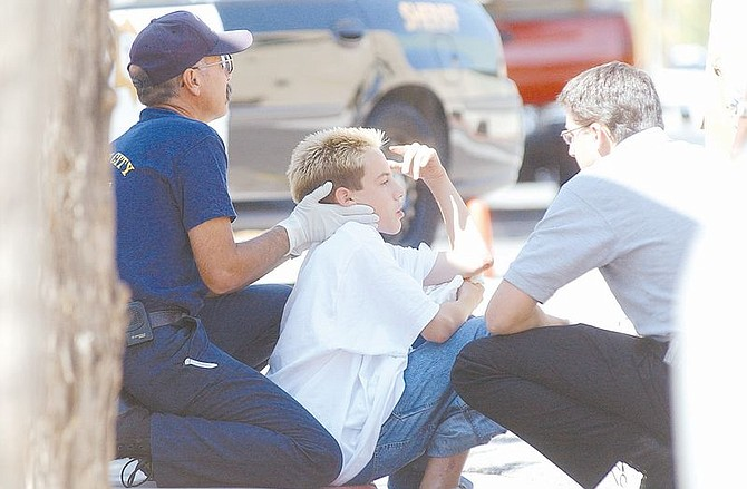 Thirteen-year-old Steven Goodwin is looked after by Carson City paramedics after being hit by a truck at the intersection of Curry St. and Musser St. Tuesday afternoon.  Goodwin was riding the wrong way down a one-way street and received minor injuries. His bike was toast.