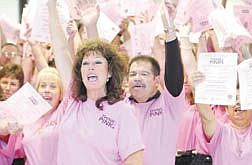 Carson City adminstrated assistant, Liz Teixeira, center left, and Juan Guzman, behind right wave their hands during a video taping of the Think Pink gathering at Carson City Hall Tuesday afternoon. The group is part of a Carson effort to bring awareness to benefits of early detection in breast cancer. photo by Rick Gunn