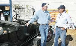 """Purina Mills District Manager John Link, left, talks with Bill Williamson of Carson City on Monday morning at S&W Feeds.  Williamson's driving dog Budd won the Purina Mills """"People and Their Amazing Animals"""" summer national pet talent competition for Budd's ability to drive Williamson's Model T.  Budd was killed by a hit-and-run driver in August."""