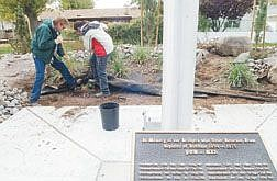 Left to right Carson City parks maintenance workers Bob Meitzner and Terrell Zuend work on a section of landscaping surrounding  the Vietnam Memorial at Mills Park Wednesday afternoon.  Nevada State Prison Inmates have carved special memorial stones which will be in stalled at the memorial this week.